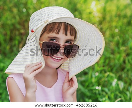 Kid smiling in sunglasses and a hat.
