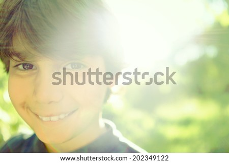 Kid smiling portrait in nature with lens flare (Note: filter applied for desired authentic instagram look) - stock photo