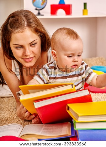 Kid son and mother baby boy lying on floor and read a lots of books.