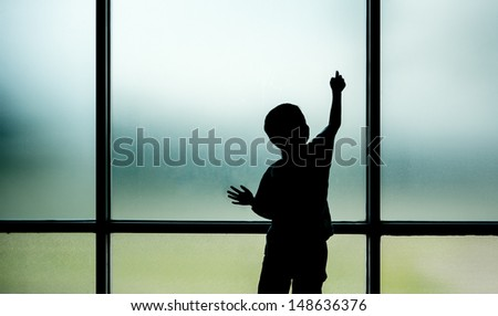 Kid standing and plays on window - stock photo