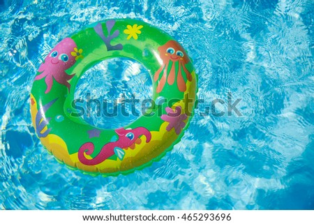 Kid swimming ring floating in  a pool on a sunny day