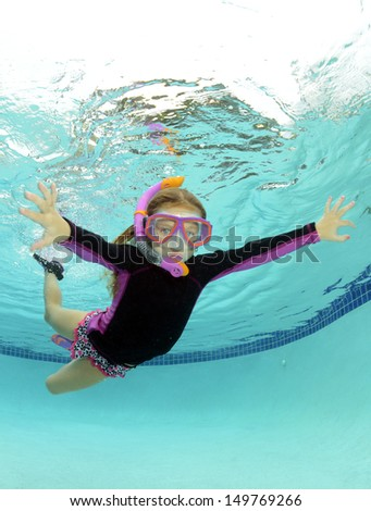 kid swimming underwater in summer in a pool - stock photo