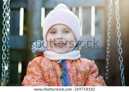 Kid swinging on a swing in the yard. - stock photo