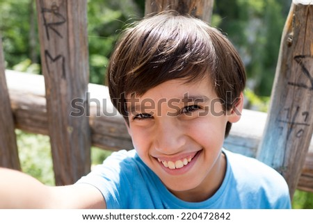 Kid taking selfie in nature - stock photo