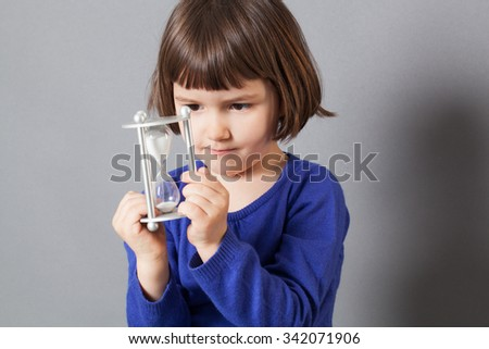 kid time concept - concentrated preschool child enjoying learning about time, holding an egg timer for innocence and future,studio shot - stock photo