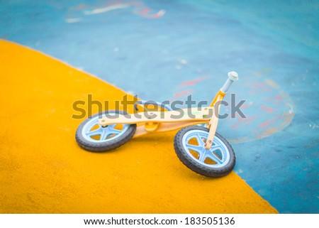 Kid toy bike abandoned and on the asphalt ground - stock photo