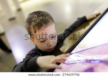 Kid using touch screen in the museum - stock photo