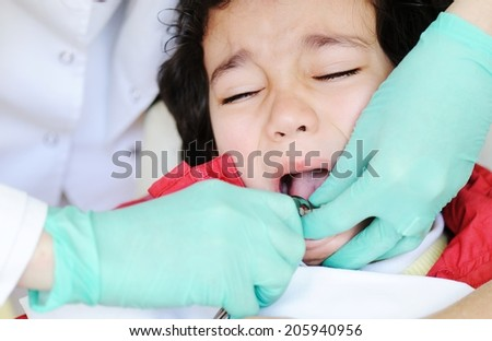 Kid visiting dentist office in hospital for pulling out milk tooth - stock photo