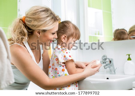 kid washing hands with mom - stock photo