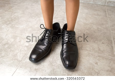kid wearing the father shoes lik - stock photo