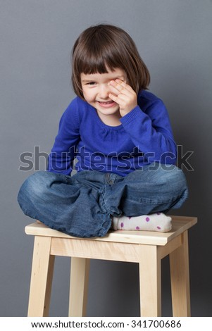 kid wellbeing concept - thrilled preschool child sitting with relaxing crossed legs expressing healthy childhood,studio shot - stock photo