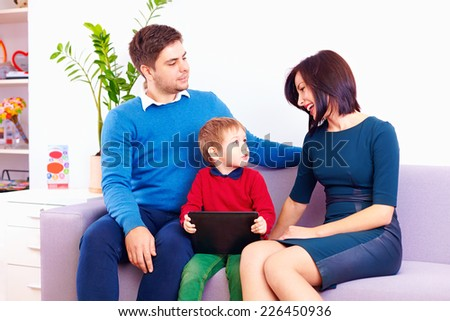 kid with digital tablet talking to parents - stock photo