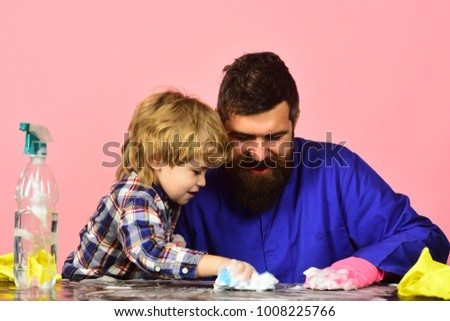 Kid with father cleaning together with sponges. Man with smiling face and cute child on pink background. Guy with beard and mustache in rubber glove at table. Cleaning activities concept.