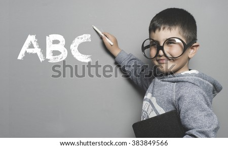 kid with goggles and funny gesture writing on the blackboard the text abc