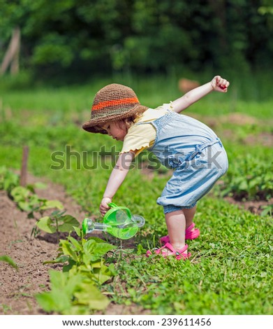 Kid with hat pouring water to vegetable - stock photo