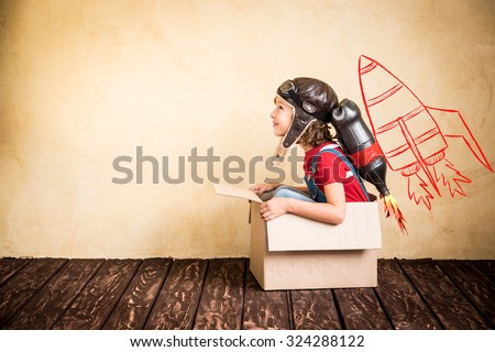 Kid with jet pack. Child playing at home. Success, leader and winner concept - stock photo