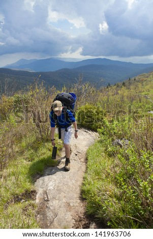 kid with large backpack hiking through mountains - stock photo