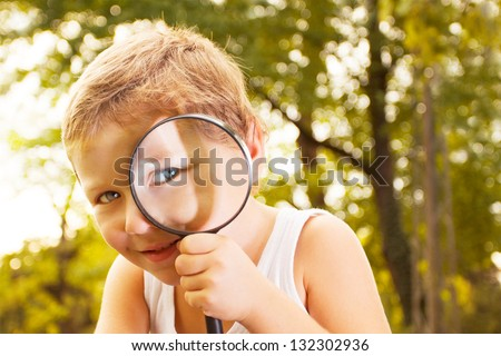 Kid with magnifying glass. - stock photo