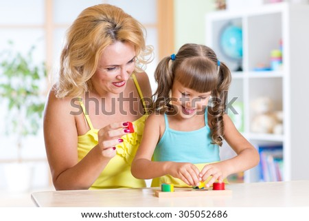kid with mother playing together at table at home