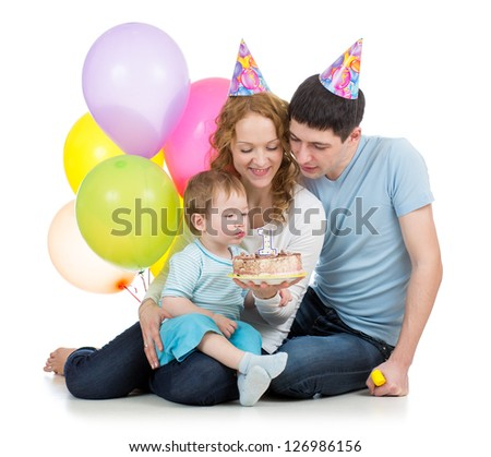 kid with parents celebrating birthday  and blowing candles on cake - stock photo