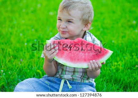 Kid with slice of watermelon, outdoors eating, picnic
