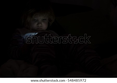 Kid with tablet sitting on bed and watching cartoons at night.