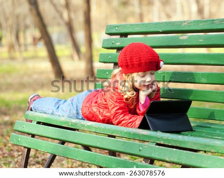 Kid with technology outdoors in the park - stock photo