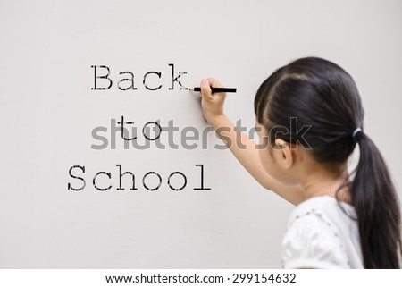 Kid write black color back to school on wall with blur face