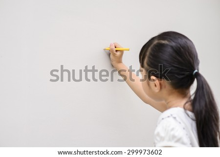 Kid write yellow font on wall with smiling face - stock photo