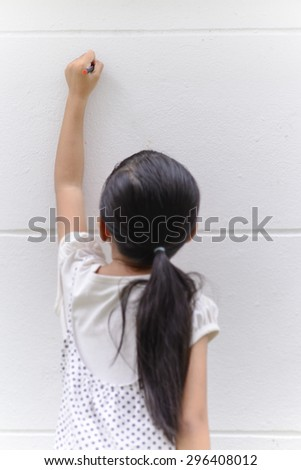 Kid writing on wall with her black pencil - stock photo