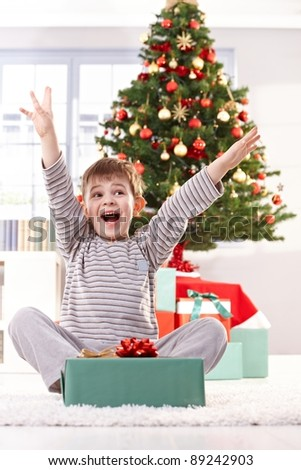 Kid yelling happily at christmas gift with arms raised, sitting at christmas tree in morning.? - stock photo