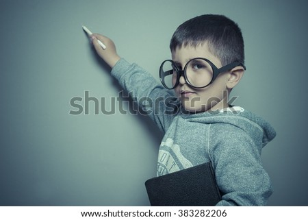 kid, young student writing on a blackboard school with a book in hand and big glasses