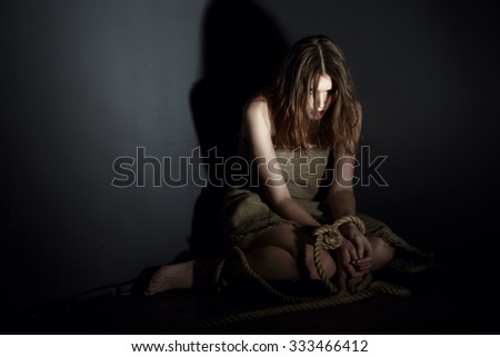 Kidnaping concept. Exhausted model with tied hands - stock photo