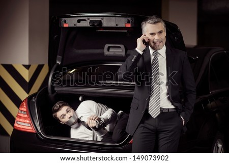 Kidnapped man. Tied up businessman lying in the car trunk and looking at camera while kidnapper talking at mobile phone - stock photo