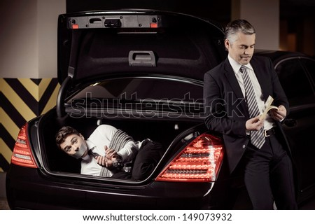 Kidnapped man. Tied up businessman lying in the car trunk and looking at camera while kidnapper counting money near him - stock photo