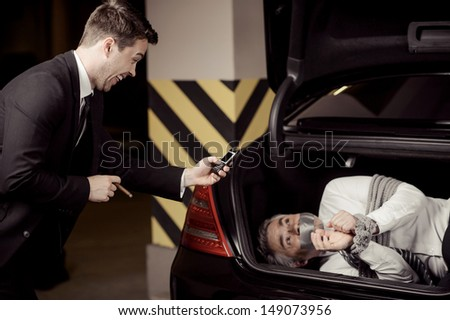 Kidnapped man. Tied up businessman lying in the car trunk and looking at kidnapper shooting him at his mobile phone camera - stock photo