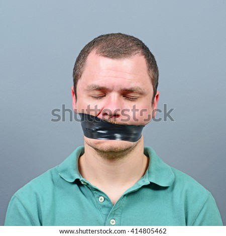 Kidnapped man with tape over his mouth - stock photo