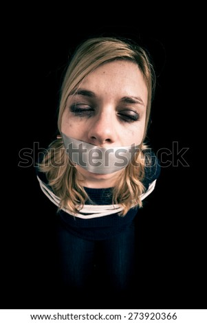 Kidnapped woman hostage with tape over mouth and tied up with rope - stock photo