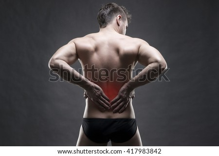 Kidney pain. Man with backache. Handsome muscular bodybuilder posing on gray background with red dot - stock photo