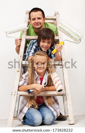 Kids and their father getting ready to paint the room - equipped with paint roller and ladder - stock photo