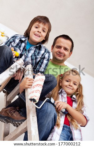 Kids and their father ready to paint the room - on the ladder with painting rollers - stock photo