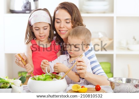 Kids and their mother are preparing salad - stock photo
