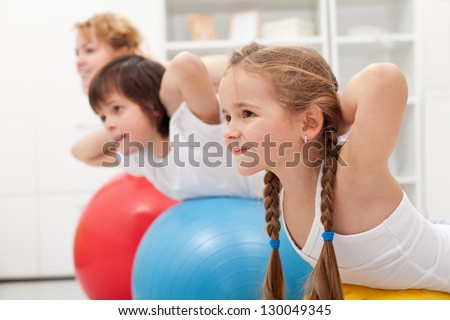 Kids and woman doing gymnastic exercises with balls - stretching their back