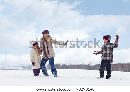Kids and woman enjoy the snow having a snowball fight - stock photo