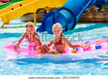 Kids are floating on inflatable mattress in water park. Summer holiday.
