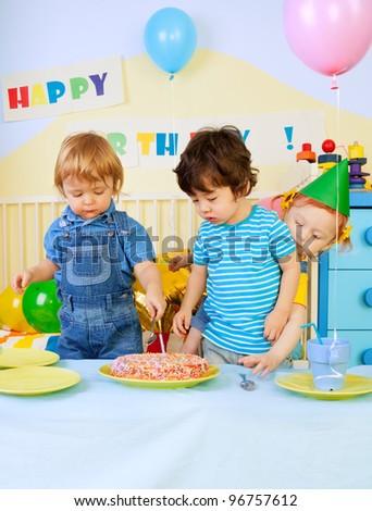 Kids around birthday cake on birthday party - two boys and girl - stock photo
