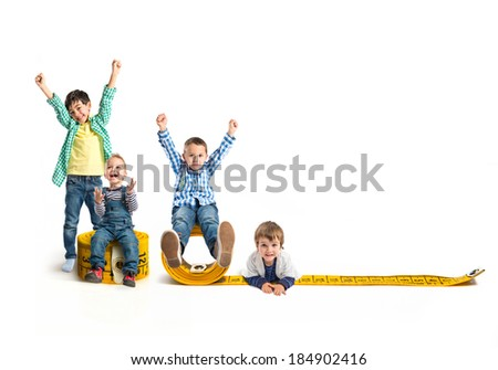 Kids around tape measure isolated over white  - stock photo