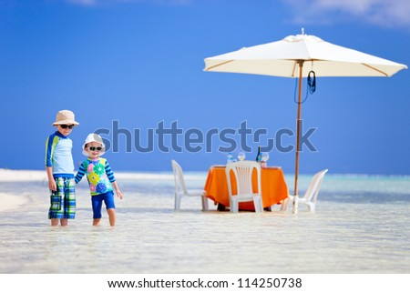 Kids at exotic island picnic with table set in a shallow water