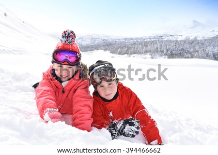 Kids at ski resort laying down in snow