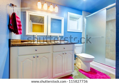 Kids Bathroom with blue walls,  pink rug and towel. - stock photo